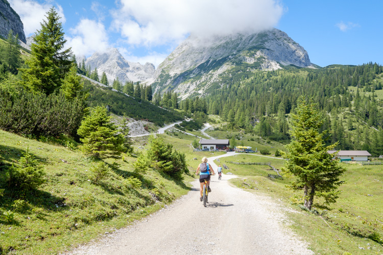 photo showing Cyclists Approaching The Seebenalm Restaurant With The Sonnenspitze Mountain Behind In The Mieminger