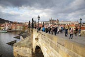 Thumbnail image of tourists walk on the Charles Bridge under a stormy sky, Prague, Czech Republic