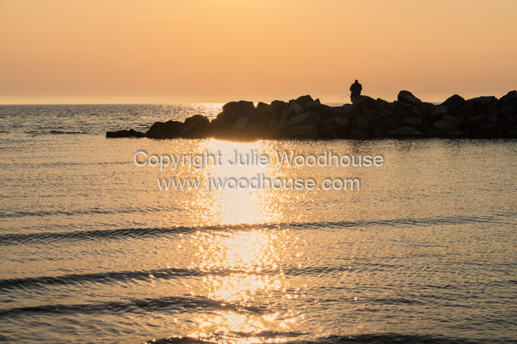 photo showing Sunset Over The Sea At Ahrenshoop Man Sea Fishing Off Rocks, Mecklenburg-Vorpommern, Germany