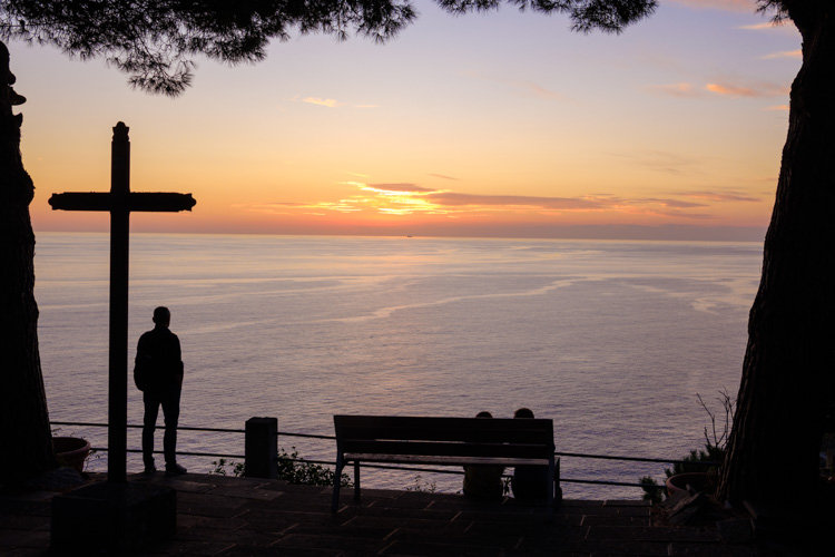 photo showing Man Viewing The Sunset View Of The Coast By A Cross From Riomaggiore, Cinque Terre, Liguria, Italy